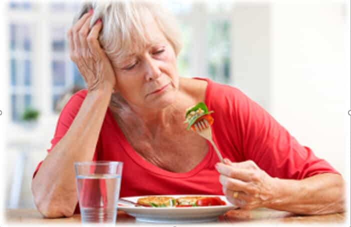 An elderly women trying to eat
